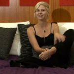 A woman with short pixie style blonde hair is sitting on a bed facing the camera.  She is wearing a black tank top and black pants.  Her left foot is raised a little to show the camera.