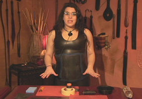 A woman with long dark hair, glasses, a large pendant on a necklace and wearing a black latex tank dress.  She is standing behind a table covered with her supplies.