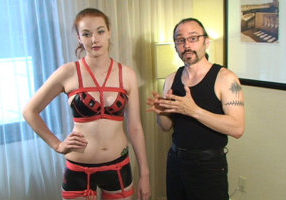 A man with his hair in a ponytail, goatee, glasses and wearing black pants and a black tank top is standing next to a woman. She is wearing a black and red leather bra, black boy shorts and red rope. She has one hand on her hip and he is speaking to the camera.