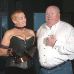 A man in a white button down shirt and jeans is standing next to a woman in a black bustier.