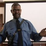 A man is wearing a blue police-style shirt, tie, and leather strap diagonally across his chest. He is standing and speaking into the camera.