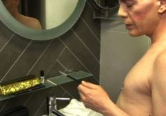 A man with a shaved head and face. He is shirtless and  stands in front of a bathroom mirror.  He is facing the mirror and holding and eyeshadow brush in hes left hand.