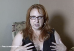 A woman with long red hair, glasses and wearing a black sleeveless top is speaking to the camera.