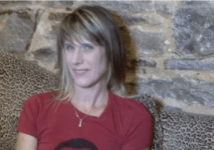 A woman in a red t-shirt with shoulder length blonde hair and bangs sits on a leopard print couch in front of stone wall. She is speaking to the camera.