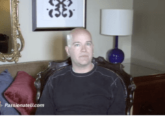 A man with a shaved head, wearing a black long-sleeved shirt is sitting on a leather chair and speaking to the camera.