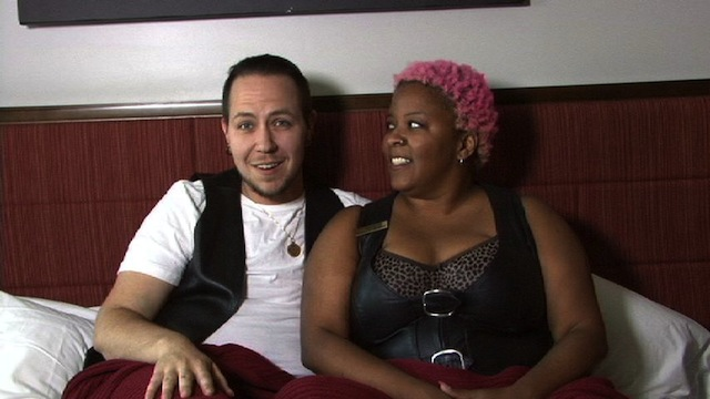 A man in a white t-shirt and black leather vest is sitting on a bed next to a woman with closely cropped pink curly hair, wearing a black tank dress.  They are speaking to the camera.