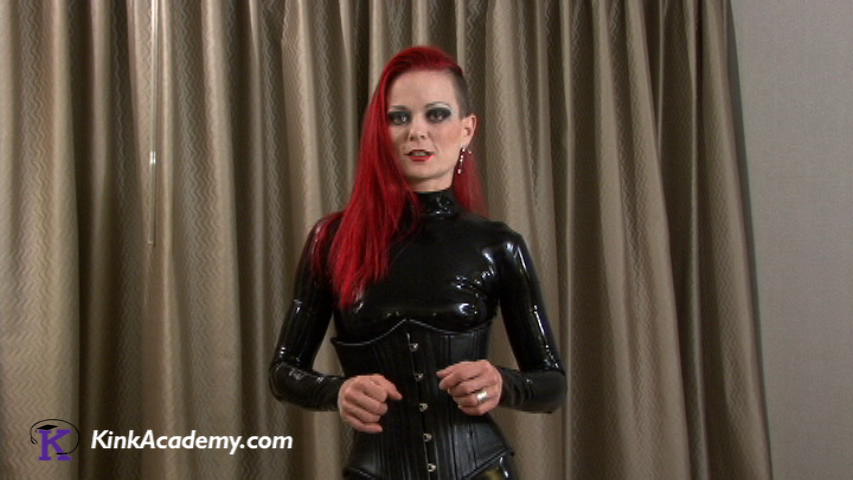 A woman in a black rubber body suit, long red hair with the left side shaved is standing and speaking to the camera..