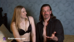 a white blonde woman wearing a black bra smiles and looks to the right where a white man with shoulder-length brown hair and a goatee talks to the camera. He is wearing a black shirt unbuttoned, and both of them sit on a bed.
