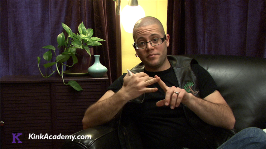 A person with a shaved head and glasses is wearing a black t-shirt and black leather vest. They are sitting on a black chair in front of purple curtains and speaking into the camera.