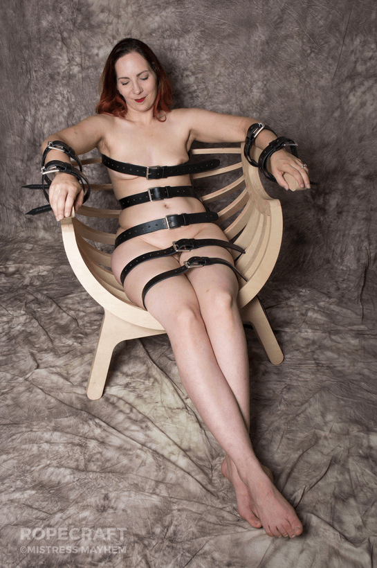 a naked woman reclines smiling in a wooden chair with several leather straps holding her in.