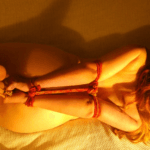 A naked woman seen from above is tied arms, wrists, and ankles with red rope.