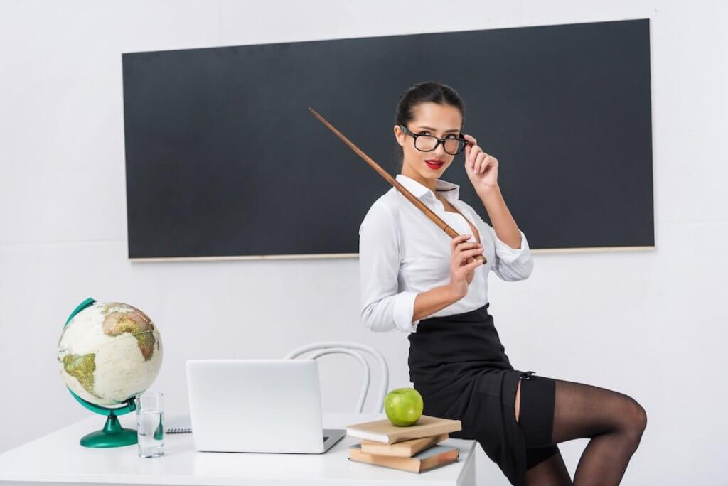 A woman with a pointer dressed in a tight skirt, white blouse, and stockings peers over her glasses as she sits on a teacher's desk.