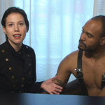 A man and a woman are sitting behind a desk. She has short dark hair and is a black button down shirt.  He is has a shaved head and stubble. He is wearing suspenders. They are speaking to the camera.