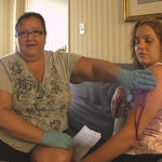 There is a side view of a woman sitting on a couch. She has her right arm exposed to show a line of blood. A woman with dark hair pulled back, latex gloves and a grey t-shirt is sitting next to her. This woman is speaking to the camera.