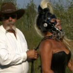 A man in a cowboy hat, white button down shirt and jeans is standing behind a woman in a black bustier and black leather pony gear.