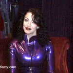 A woman with shoulder length, dark, wavy hair is standing in front of some clothing on hangers.  She has dark lipstick and is wearing a jewel tone purple  latex catsuit.