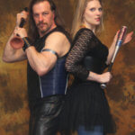 A man with long hair, a goatee, and wearing leather pants and leather vest is standing back to back with a woman.  She has long blonde hair, blue leggings and a black frilly mini dress.  He is holding a plunger in both hands and she has a small metal bat.